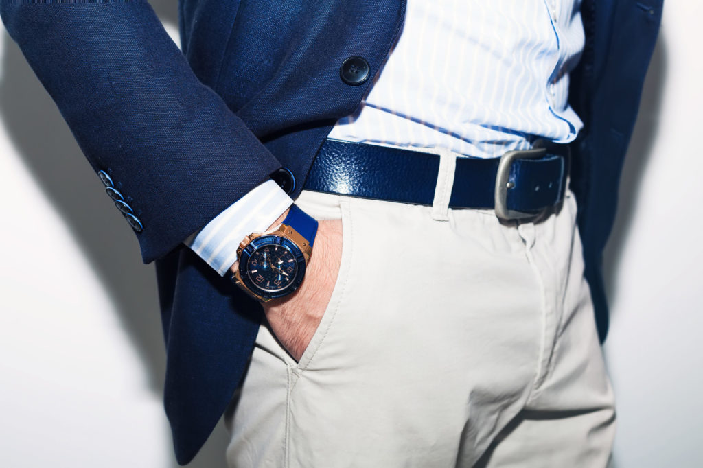 Closeup fashion image of luxury watch on wrist of man.body detail of a business man.Man's hand in a white shirt and blue jacket in a pants pocket closeup