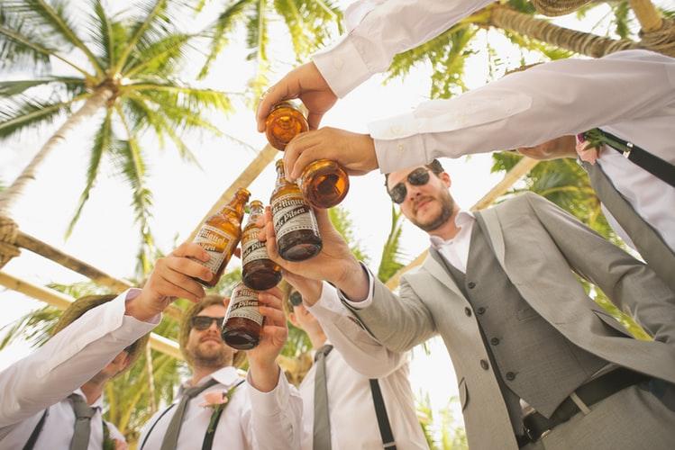 a group of men raising beer bottles
