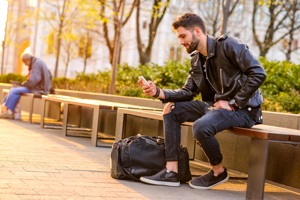 A Handsome Young Hipster Man Sitting On A Bench